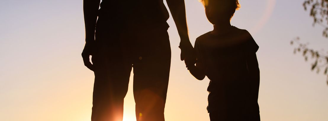 father holding child hands by sunset